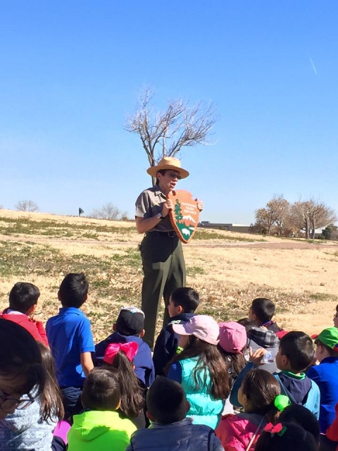 Ranger holding a National Park Service arrowhead plaque while talking to a group of students at Chamizal National Monument
