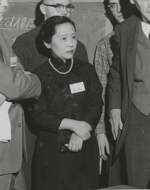 Black and white photo of Chien-Shiung Wu, surrounded by other scientists