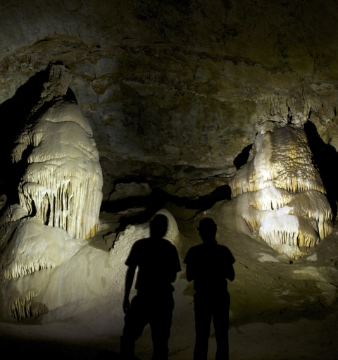 Two people in Coronado Cave standing in front of two flashlight-lit formations