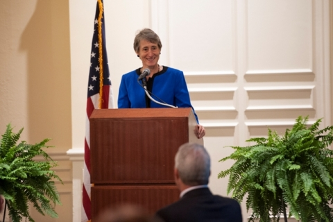 Woman in blue suit stands at podium to give speech