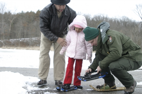 Ranger helps a child into snowshoes at Cuyahoga Valley National Park