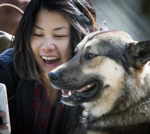 woman taking a photo of herself and a dog