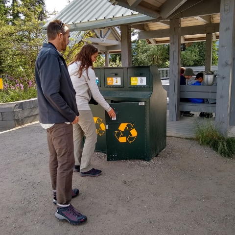 Two park visitors use the green recycling bins at a park rest stop