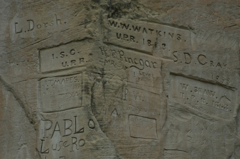 Several inscriptions are carved into El Morro's sandstone rock, many etched into smoothed boxes with names reading Watkins, Dorsh, Mapes, Pinegar, Cray, and Shaw