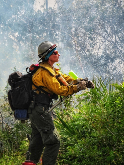 A woman in fire-safe gear and a hard hat looks to the right