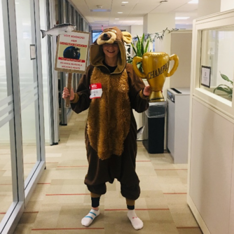 "Person dressed in a bear costume, holding a trophy and a sign for ""Fat Bear Week"""