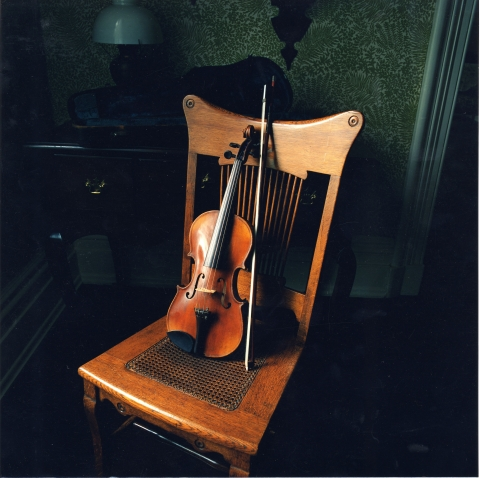 A small violin and a bow sit upright on a wooden chair