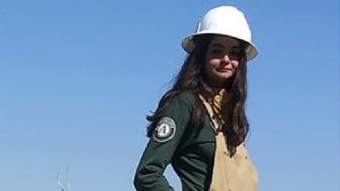 A young woman stands, wearing overalls and a long sleeve tshirt, a hardhat, and sunglasses