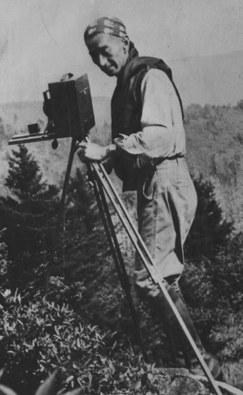 Black and white portrait of George Masa standing behind an old large-format camera at Great Smoky Mountains National Park