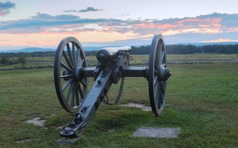 Photo of Gettysburg National Monument cannon, with setting sunset behind