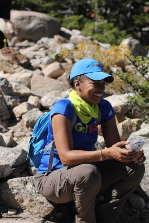 Smiling African American woman sitting on a rock wearing a blue GirlTrek t-shirt and hat