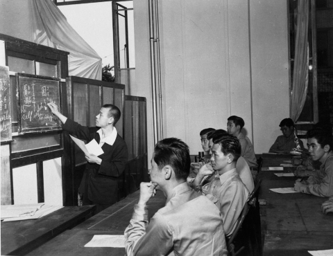 Black and white photo of a class at MISLS. An instructor writes on a blackboard in front of two rows of students sitting at tables.