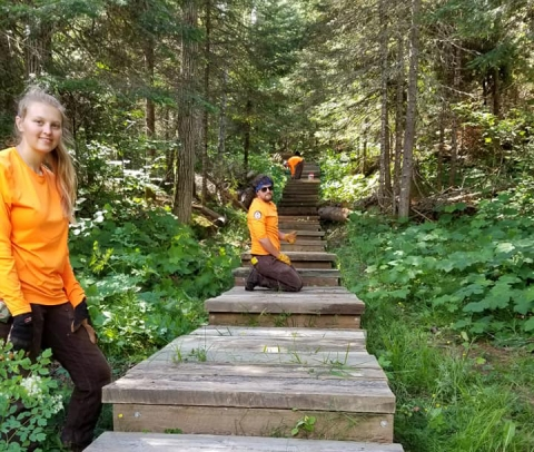 Three students in orange shirts pose on climbing timber steps among many green trees