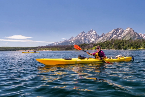 A woman paddling in a yellow single kayak on the blue water in front of the mountainous Grand Tetons