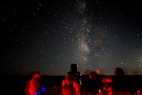 People in red light behind telescopes looking at the Milky Way in the dark sky