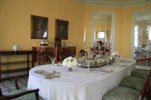 A formal dining room table is set with a vase of white flowers and long white taper candles. On the pale yellow walls hang two portraits.