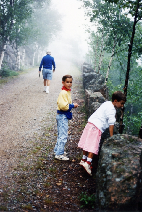 Two young children stop along a gravel path, lined with trees. Ahead of them, a man in a sweatshirt and hat walks further down the path, leading the way.