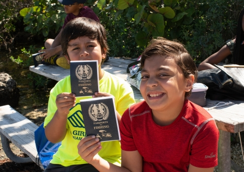 Young kids holding Passport to Fishing booklets as part of the Junior Ranger Angler Program with NPS