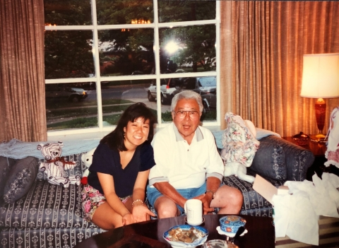 A young woman sits on a couch with her grandfather, both smiling at the camera.