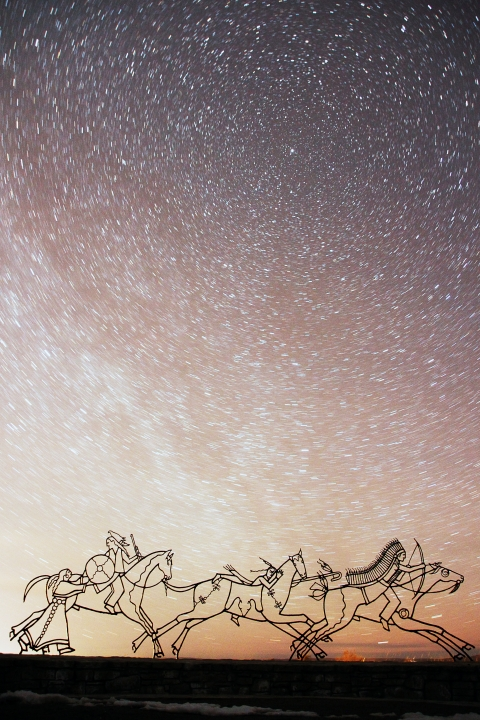 Wire-framed sculptures of Native Americans riding horses silhouetted against a starry night sky over Little Bighorn Battlefield National Monument