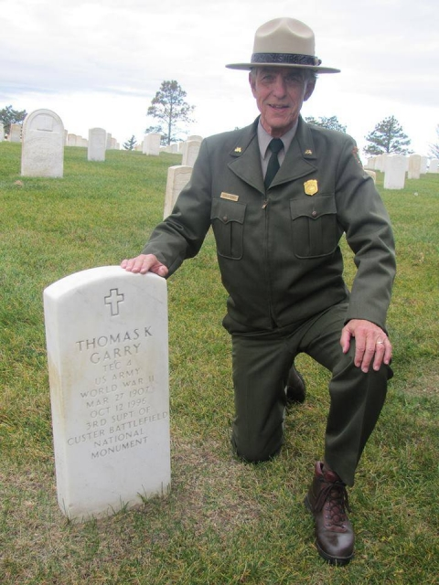 Park ranger kneeling next to a tombstone at Little Bighorn Battlefield National Monument