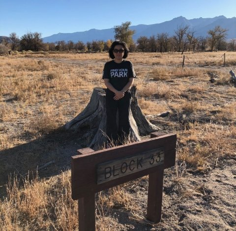 "Kim Hirose Tobe stands behind the sign that reads ""Block 33"" at Manzanar National Historic Site"