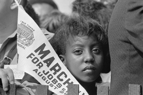 A protester looks at the camera and holds a pennant flag for the March on Washington