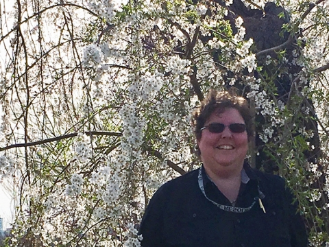 Megan Springate smiles in front of blooming cherry blossom trees