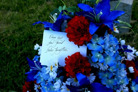 "Red, white, and blue bouquet of flowers with a card reading ""Once Lost, Now Found, Never Forgotten"""