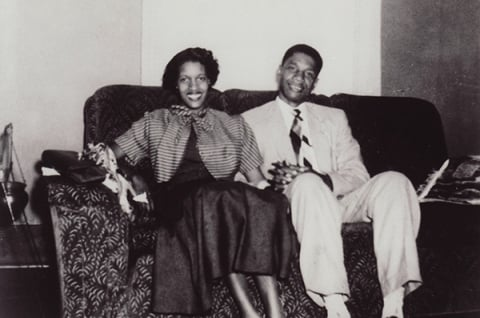 Black and white photo of Myrlie and Medgar Evers sitting on their sofa