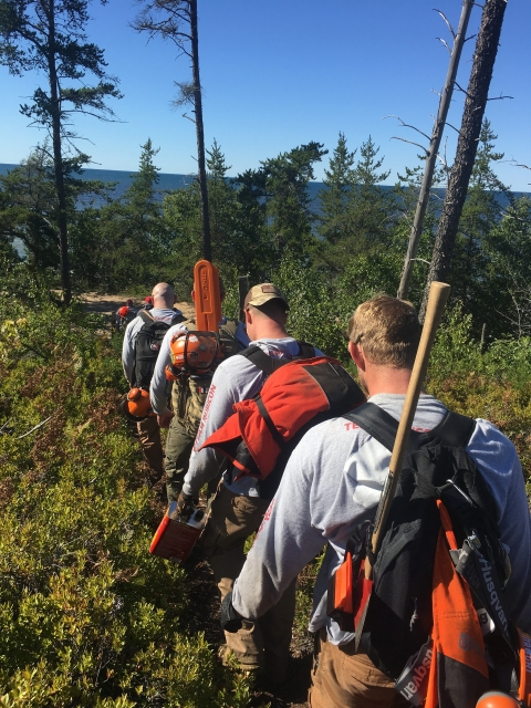 A line of guys with chainsaws, axes, and other trail work gear walking through shrubbery and trees on North Country National Scenic Trail