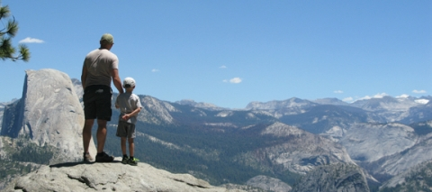 NPF staff Matt stands with this son overlooking the valley at Yosemite National Park's Glacier Point.