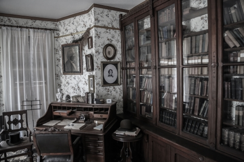 Wooden writing desk and full wooden bookshelves inside the Frederick Douglas National Historic site