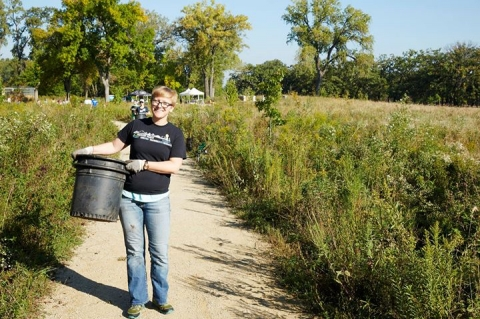 Woman holding a bucket wearing work gloves at the Mississippi National River Recreation Area
