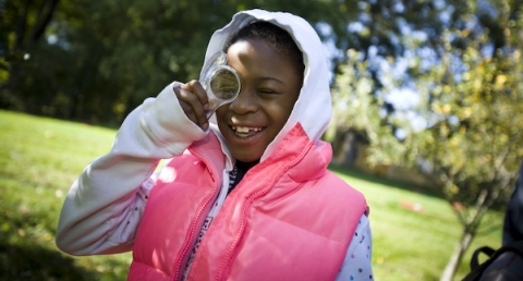 Young girl holds magnifying glass, smiling, wearing pink vest
