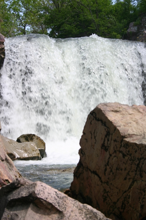 Waterfall and wet rocks in the river stream