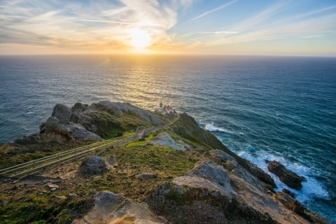 Four white-sided, red-roofed structures sit on a rocky headland above the Pacific Ocean at the base of a long stairway. Above and to the left of the lighthouse, the sun filters through wispy clouds as it descends toward the horizon