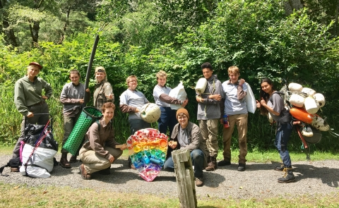 A group of service corps members pose with a rainbow NPS arrowhead, constructed from collected marine debris
