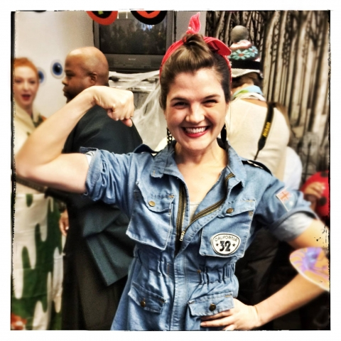 Person dressed in a Rosie the Riveter costume, with a denim shirt, rolled up sleeves, and bandana in her hair. She flexes a muscle and smiles at the camera.