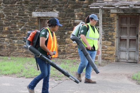 Yukary Gomez and Sarah Vergara use leaf blowers to clear paths. They wear safety vests and goggles