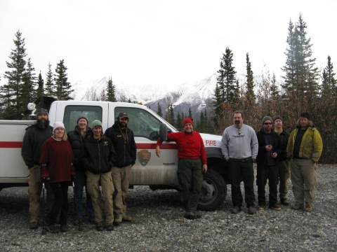 A group of people pose for a photograph in front of a truck. In the distance in the background, a snowy mountain range.