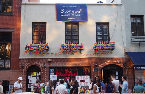 Group of people standing in front of Stonewall Inn celebrating the designation of Stonewall National Monument in New York City