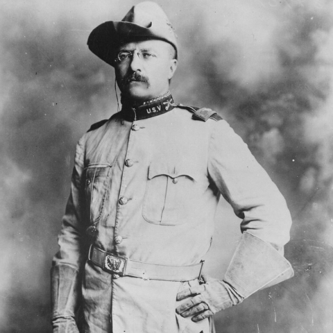 Black and white portrait photograph of Theodore Roosevelt standing, in full Rough Rider U.S.V uniform