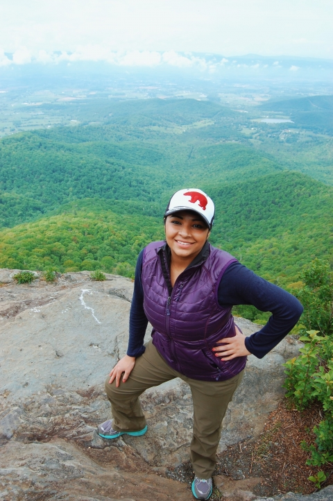 South-Asian American Ambreen Tariq posing with the green valley of Shenandoah National Park behind her
