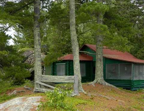 Green log Jun Fujita cabin with a red roof amongst trees at Voyageurs National Park