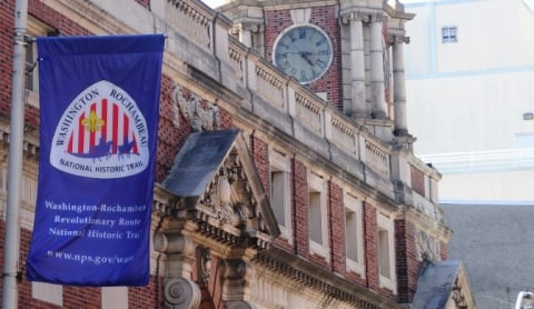 Street banner for Washington-Rochambeau Revolutionary Route National Historic Trail hanging outside a 18th century building