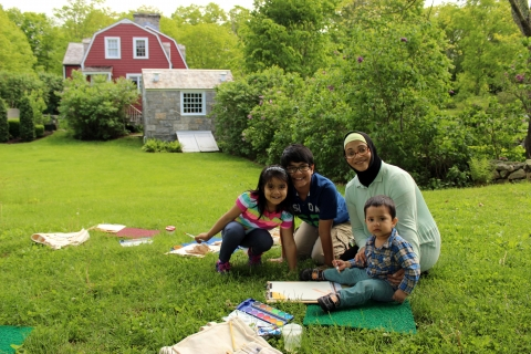 A women and three children sitting on blanket in a field creating art with watercolor paints.