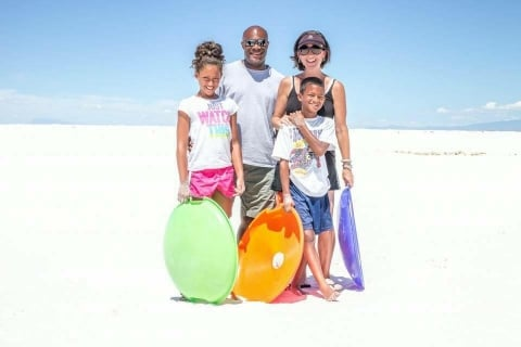 A family poses for a photo standing on white sand dunes, holding sleds
