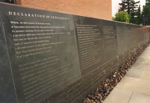 The Declaration of Sentiments and the signers names are written on a blue stone wall, which in summer months, has a calm flow of water flowing over the text.