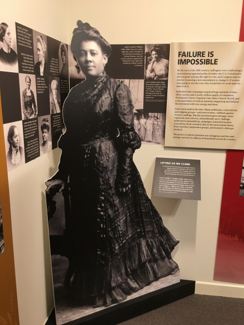 Full body cut out of Mary Burnett Talbert with a long, black dress and bun hair style. The cut out is next to the Lifting as We Climb panel.